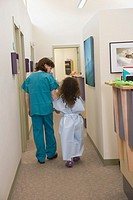 Female doctor and girl 6-8 walking down clinic corridor, rear view