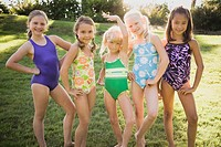 Five girls 7-10 in swimsuits standing side by side, portrait