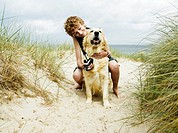 Boy 10-12 crouching on beach with dog on lead, smiling