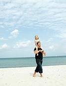 Girl 6-8 being carried on father´s shoulders on beach, smiling