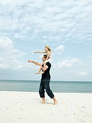 Father carrying daughter 6-8 on shoulders on beach, both pointing