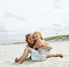 Mother embracing daughter 6-8 on sandy beach, smiling, portrait