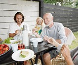Three generational family eating lunch in garden, smiling