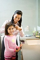 Mother fixing daughter´s 5-7 hair in bathroom
