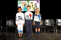Three children 7-9 standing on stage at spelling bee competition
