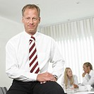Businessman sitting on desk in office, portrait