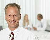 Businessman in office, smiling, portrait, close-up