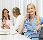 Businesswoman on mobile phone at conference table, businesspeople in background
