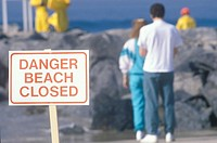 ´A sign warning, dangerbeach closed with people in the background´