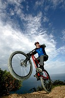 Teenage boy 14-15 on mountain bike doing wheelie on cliff top