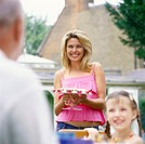 Woman Stands Near Her Daughter Holding a Dessert While Smiling at an Elderly Seated Man