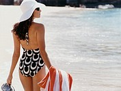 Rear View of a Woman on the Beach in a Swimsuit Carrying a Towel
