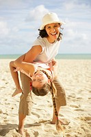 Mother holding daughter 6-8 on beach, smiling, portrait
