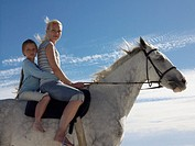 Portrait of a Woman and Her Young Daughter Sitting on a White Horse