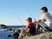 Father and Son Fishing on a Rock