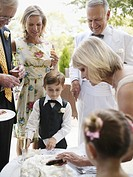 Bride serving wedding cake to pageboy 6-7 and guests