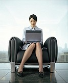 Young businesswoman sitting in armchair by window using laptop