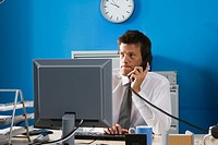 Businessman using telephone at desk