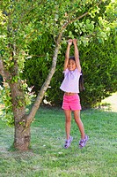 Girl 4-6 hanging from tree branch in garden, smiling, portrait