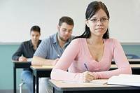 Three college students in classroom focus on woman in foreground