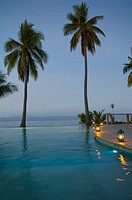 Fiji, Mamanuca Islands, Mana Island, infinity pool illuminated at dusk