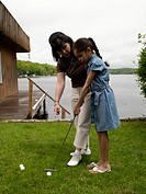 Grandmother teaching granddaughter 8-10 to golf