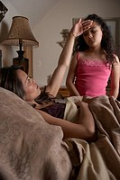 Mother in bed feeling daughter´s 8-10 forehead
