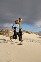 Mature couple jogging on sand dune, low angle view