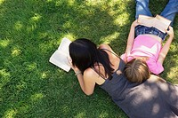 Mother and daughter 8-9 reading on grass, elevated view