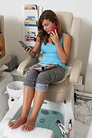 Young woman in beauty parlour, using mobile phone, close-up