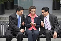 Two businessmen looking at a mobile phone in a businesswoman´s hands