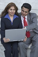 Businessman and businesswoman sitting on a marble step and looking at a laptop