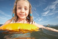 Girl 7-9 swimming with inner tube in sea