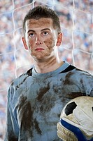 Soccer goalie holding ball covered in mud in goal