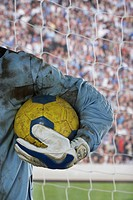 Soccer goalie holding soccer ball in goal, mid section