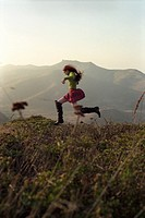 Young woman running on grassy hill in mountains