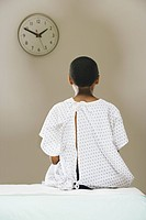 Teenage boy 12-13 sitting with surgical gown in patient room, rear view