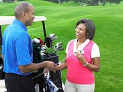 Male golfer handing golf club to woman on golf course
