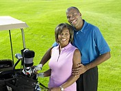 Couple standing next to golf cart on golf course, portrait