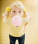 Girl 6-8 blowing bubble with gum