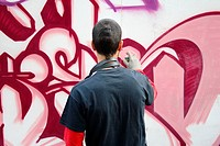 Young man painting a graffiti