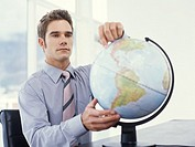 Businessman pointing at west coast of the USA on globe
