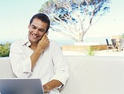Man outside using mobile phone and laptop, smiling