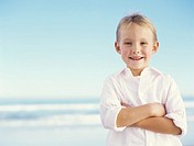 Boy 5-7 on beach with arms crossed, smiling, portrait