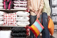 Couple standing beside shelf in shop, carrying orange cushions, hands behind back, rear view