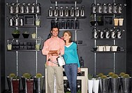 Couple shopping in garden centre, man carrying watering can, indoors, portrait