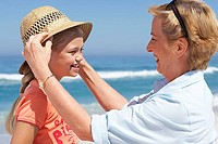 Grandmother placing sun hat on granddaughter's 7-9 head at beach, smiling, side view