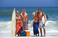 Four young friends standing on sandy beach with surfboards, portrait, sea in background