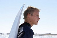 Young man standing on beach, wearing wetsuit, surfboard behind back, profile