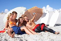 Four young friends relaxing on sandy beach, man taking photograph with digital camera, smiling
